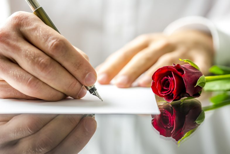 Closeup of the hands of a romantic man writing a love letter to his sweetheart for Valentines Day to be accompanied by a single beautiful fresh red rose