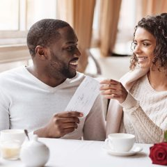 african american couple sharing a gift at a cafe