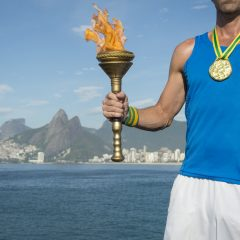 man carrying olympic torch and wearing gold medal