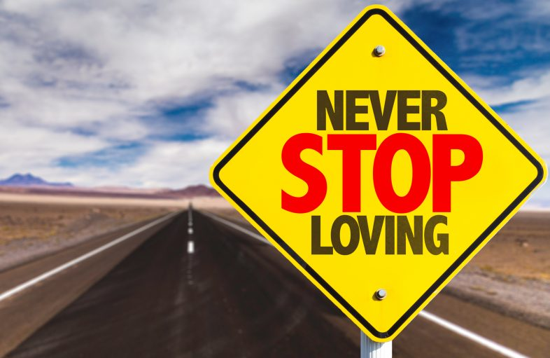 "Yellow sign on road that reads ""Never Stop Loving"""