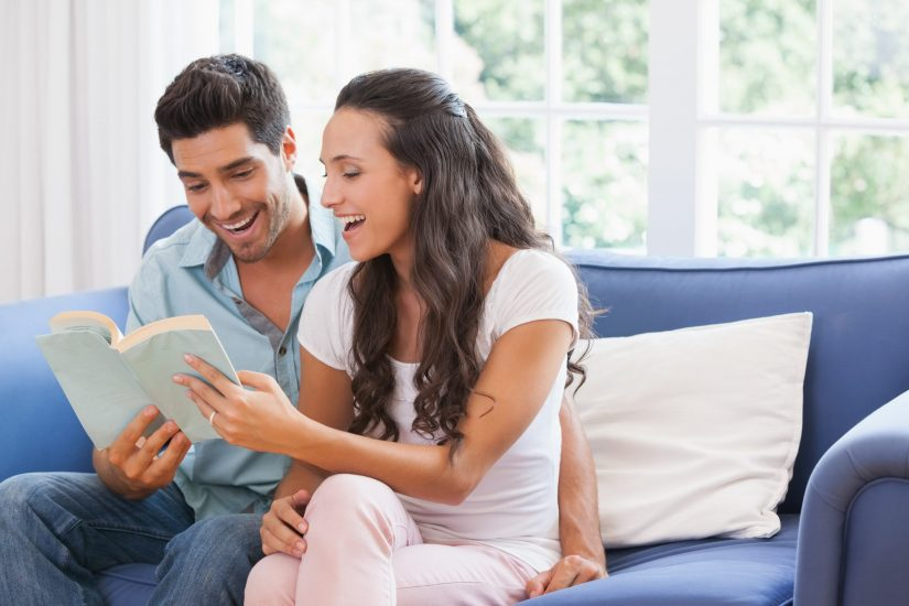 couple reading love songs on the sofa at home in living room